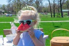 Petite fille dans les lunettes de soleil et le diadème mangeant la pastèque photographie stock