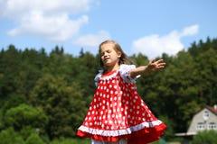 Petite fille dans un bain de soleil à pois rouge Images libres de droits