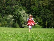 Petite fille dans un bain de soleil à pois rouge Photos libres de droits