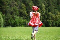 Petite fille dans un bain de soleil à pois rouge dans une course importante sur Image libre de droits
