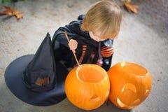 Petite fille dans un costume d'une sorcière s'asseyant près de deux potirons, h Photos libres de droits