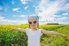 Petite fille dans un domaine de graine de colza Photographie stock