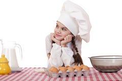 Petite fille dans un tablier blanc près de la boîte avec des oeufs Image stock