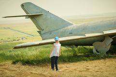 Petite fille dans une casquette de baseball à l'aéroport près des vieux avions militaires Photographie stock