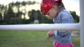 Petite fille dans une casquette de baseball élégante essayant de se boutonner vers le haut de son jaket de jute au coucher du sol banque de vidéos