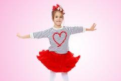 Petite fille dans une jupe rouge et arc sur sa tête images libres de droits