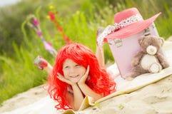 Petite fille dans une perruque se trouvant sur l'herbe Photographie stock libre de droits