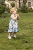 Petite fille dans une robe lilas avec les cheveux blonds Images stock