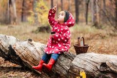 Petite fille dans une veste de pois se reposant sur un arbre et un thé potable images stock