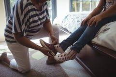 Petite-fille de aide de grand-mère pour porter des chaussures dans la chambre de lit Photographie stock