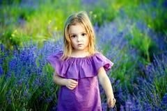 Petite fille de petite fille dans une robe rose regardant le mal et le regard triste, pendant l'été sur un fond de champ fleuriss images stock