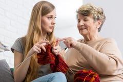 Petite-fille de enseignement de grand-maman comment tricoter images stock