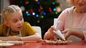 Petite-fille de enseignement de mamie pour décorer des biscuits de pain d'épice avec du sucre glace banque de vidéos