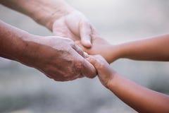 Petite fille de grand-mère et d'enfant tenant la main ensemble Photos libres de droits