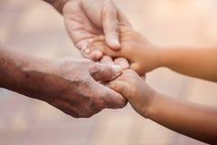 Petite fille de grand-mère et d'enfant tenant la main ensemble Photos stock