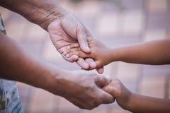 Petite fille de grand-mère et d'enfant tenant la main ensemble Images stock