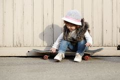 Petite fille de hippie avec le portrait de planche à roulettes Photographie stock libre de droits
