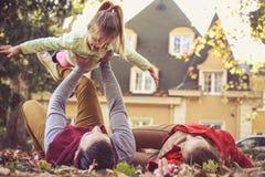 Petite fille de mouche Père jouant avec le descendant Photographie stock libre de droits