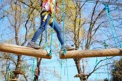 Petite fille de plan rapproché jouant au parc d'aventure montant et relevant des défis d'équilibre pour l'amour-propre image libre de droits