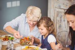 Petite-fille de portion de grand-mère tout en prenant le petit déjeuner Photos stock