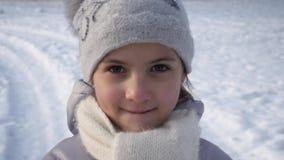 Petite fille de portrait sur le fond de la terre couverte de neige banque de vidéos