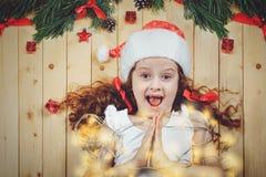 Petite fille de prière avec une guirlande de fête sur le fond en bois Image libre de droits