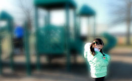 Petite fille de renversement isolé sur le terrain de jeu Photographie stock libre de droits