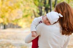 Petite fille de sommeil sur l'épaule de la mère Photo libre de droits