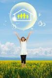 Petite fille de sourire affichant sur le symbole de famille dans la grande bulle de savon Image stock