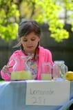 Petite fille de sourire au stand de citronnade en été Photographie stock libre de droits
