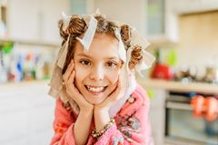 Petite fille de sourire avec des bigoudis de cheveux sur sa tête Images libres de droits