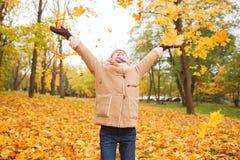 Petite fille de sourire avec des feuilles d'automne en parc Photo stock