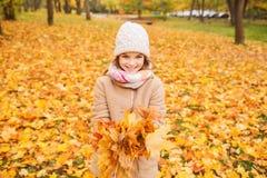 Petite fille de sourire avec des feuilles d'automne en parc Photos stock