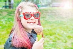 Petite fille de sourire avec des lunettes de soleil mangeant la crème glacée au parc image libre de droits