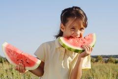 Petite fille de sourire avec deux parts de pastèque Image stock
