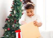 Petite fille de sourire avec la boîte-cadeau Photos libres de droits
