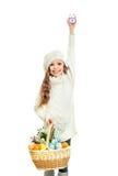 Petite fille de sourire avec le panier plein des oeufs de pâques colorés Photos stock