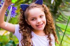 Petite fille de sourire bouclée heureuse jouant avec des bulles de savon sur une nature d'été, port oreilles bleues des accessoir Photographie stock