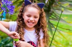 Petite fille de sourire bouclée heureuse jouant avec des bulles de savon sur une nature d'été, port oreilles bleues des accessoir Image libre de droits
