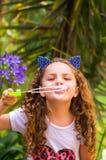 Petite fille de sourire bouclée heureuse jouant avec des bulles de savon sur une nature d'été, port oreilles bleues des accessoir Images libres de droits