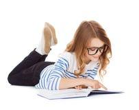 Petite fille de sourire d'étudiant se trouvant sur le plancher Photo stock