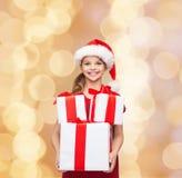 Petite fille de sourire dans le chapeau d'aide de Santa avec des cadeaux Photos libres de droits