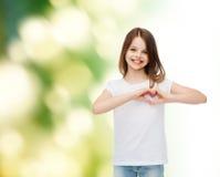 Petite fille de sourire dans le T-shirt vide blanc Photos libres de droits