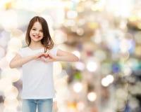 Petite fille de sourire dans le T-shirt vide blanc Photo libre de droits