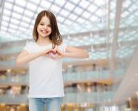 Petite fille de sourire dans le T-shirt vide blanc Images libres de droits