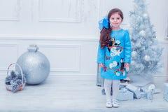Petite fille de sourire dans une robe grise dessus Photo stock