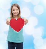 Petite fille de sourire donnant le coeur rouge Photos stock