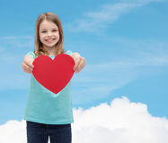 Petite fille de sourire donnant le coeur rouge Images stock