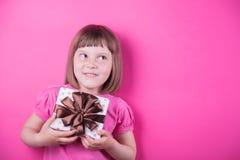 Petite fille de sourire drôle tenant le boîte-cadeau assez repéré dans des ses mains sur le fond rose lumineux Image libre de droits