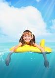 Petite fille de sourire drôle avec les verres de plongée flottant l'inflatabl Photographie stock libre de droits
